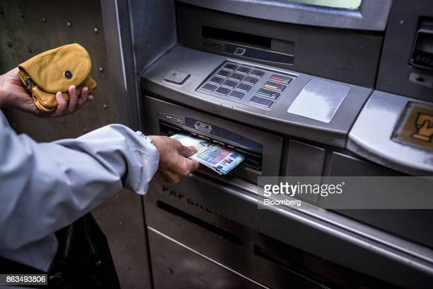 A customer withdraws 150 euros in cash from an automated teller machine operated by Banco de Sabadell SA in Barcelona Spain on Friday Oct 20 2017 In...