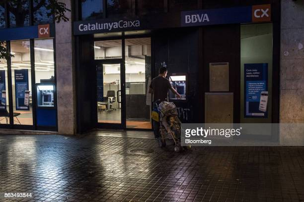 A customer withdraws cash from an automated teller machine operated by Banco Bilbao Vizcaya Argentaria SA bank branch in Barcelona Spain on Friday...