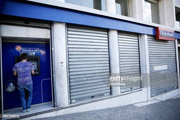 A customer withdraws cash from an automated teller machine outside a shuttered branch of Eurobank Ergasias SA in Athens Greece on Wednesday July 15...