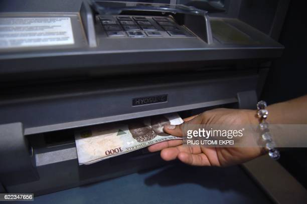 A customer withdraws Nigerian naira from an automated teller machine at a bank in Asaba Delta State Nigeria on November 10 2016 / AFP PHOTO / PIUS...