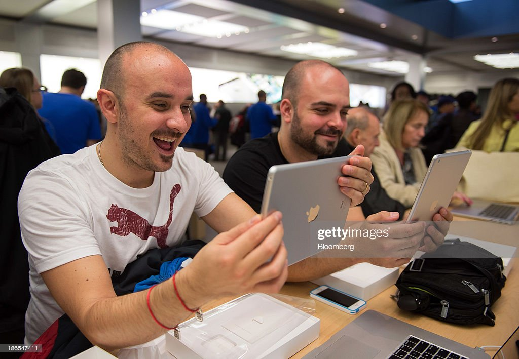 Customers Abraham Garcia, left, and George Vizziello, both visiting from Spain, check out the new Apple Inc. iPad Air at the 5th Avenue Apple store in New York, U.S., on Friday, Nov. 1, 2013. Apple Inc.'s forecast for the slowest holiday sales growth in a half decade reflects how iPhones and iPads aren't providing the growth surges they once did as competition accelerates in the saturated mobile market. Photographer: Craig Warga/Bloomberg via Getty Images