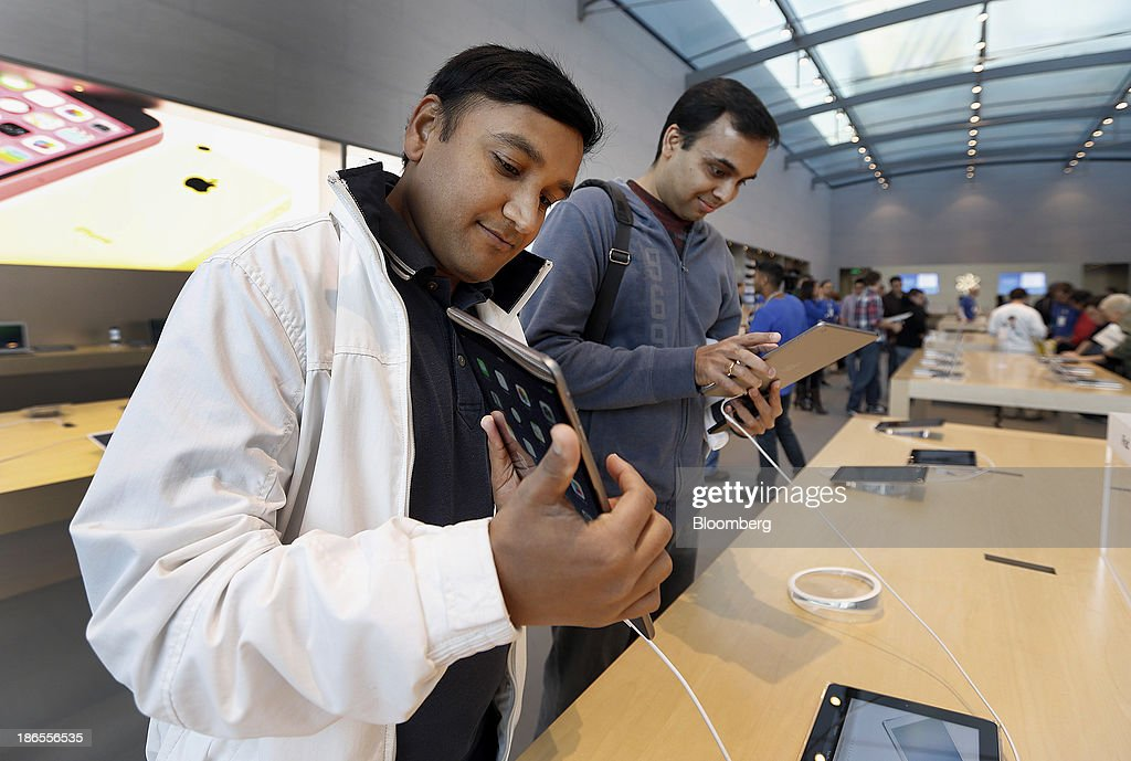 Customers Anand Inani, left, and Sanjith Thayyilthodiyil check out the new Apple Inc. iPad Air on the first day of sales of the at a store in Palo Alto, California, U.S., on Friday, Nov. 1, 2013. Apple Inc.'s forecast for the slowest holiday sales growth in a half decade reflects how iPhones and iPads aren't providing the growth surges they once did as competition accelerates in the saturated mobile market. Photographer: Tony Avelar/Bloomberg via Getty Images