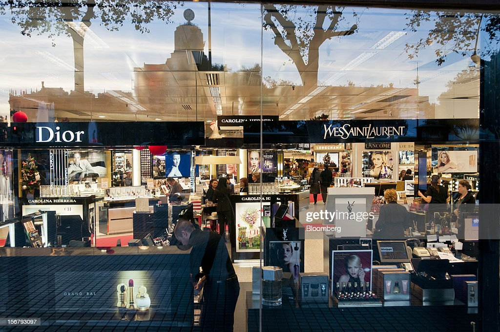 Customers and shop assistants are seen through a window in the beauty department of an El Corte Ingles department store in Barcelona, Spain, on Tuesday, Nov. 20, 2012. Bank of Spain Governor Luis Maria Linde said the government risks missing its budget targets this year and next, adding to doubts on Prime Minister Mariano Rajoy's ability to cut the deficit amid a five-year slump. Photographer: Stefano Buonamici/Bloomberg via Getty Images