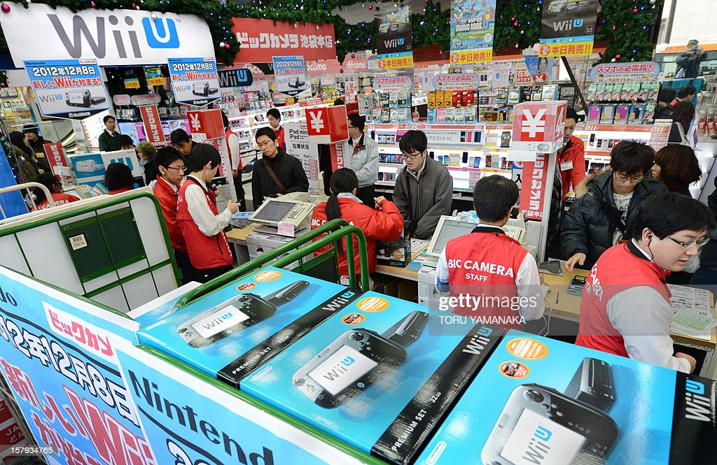 Customers are attended to by cashiers (in red) as they purchase Japanese electronics titan Nintendo's new videogame console 'Wii U' at a shop in Tokyo on December 8, 2012. Nintendo released the new console in Japan on December 8 and is hoping for a repeat of the runaway success it had with original Wii consoles, which lured legions of 'casual gamers' into the videogame world with the introduction of motion-sensing controls. AFP PHOTO/Toru YAMANAKA