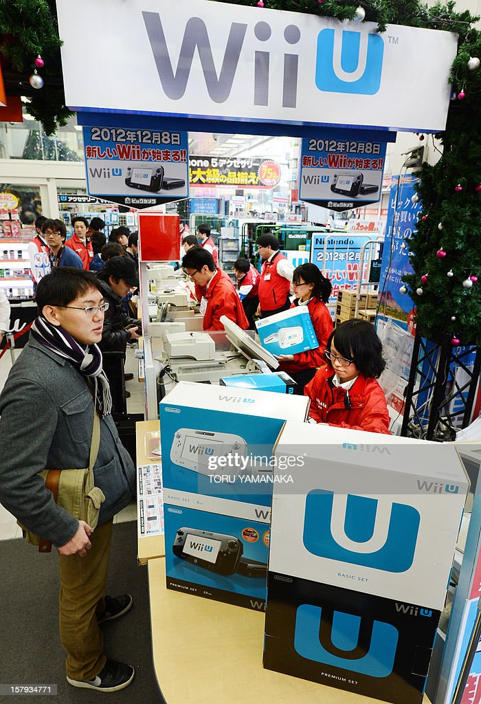 Customers (L) are attended to by cashiers as they purchase Japanese electronics titan Nintendo's new videogame console 'Wii U' at a shop in Tokyo on December 8, 2012. Nintendo released the new console in Japan on December 8 and is hoping for a repeat of the runaway success it had with original Wii consoles, which lured legions of 'casual gamers' into the videogame world with the introduction of motion-sensing controls. AFP PHOTO/Toru YAMANAKA