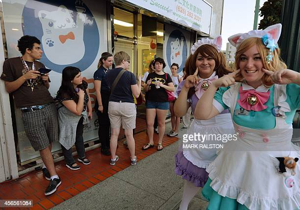Customers are entertained by staff as they line up to enter during the kickstarter opening of the Catfe in Chinatown Los Angeles on October 2 2014...