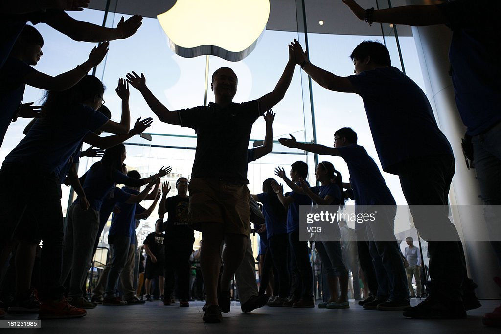 Customers are greeted by Apple store staff as they enter the Apple Store at Wangfujing on September 20, 2013 in Beijing, China. Apple starts selling two new iPhone smartphones in the Chinese mainland on Friday.