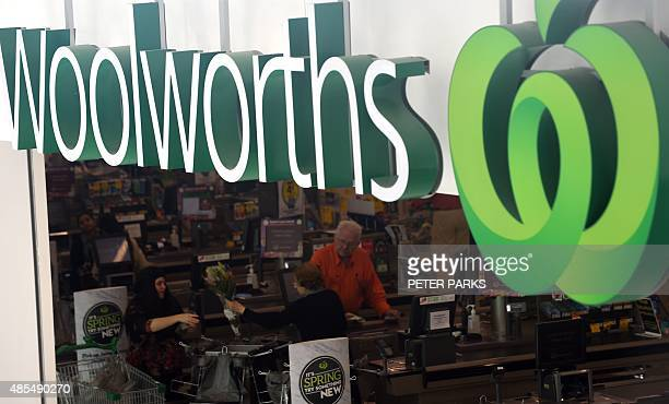 Customers are pictured at the checkout counters of a Woolworths store in Sydney on August 28 2015 Australian supermarket giant Woolworths on August...