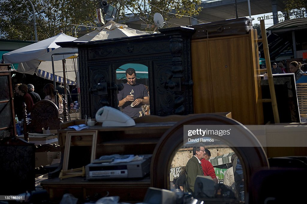 Customers are reflected in mirrors at a second hand market on November 9, 2011 in Barcelona, Spain. The current Eurozone debt crisis has left Spain with crippling economic problems. Mounting debts, record unemployment figures and the recent credit rating downgrade is leaving the country facing further economic stagnation. The people of Spain are preparing to go to the polls for a general election which will be held on November 20, 2011.