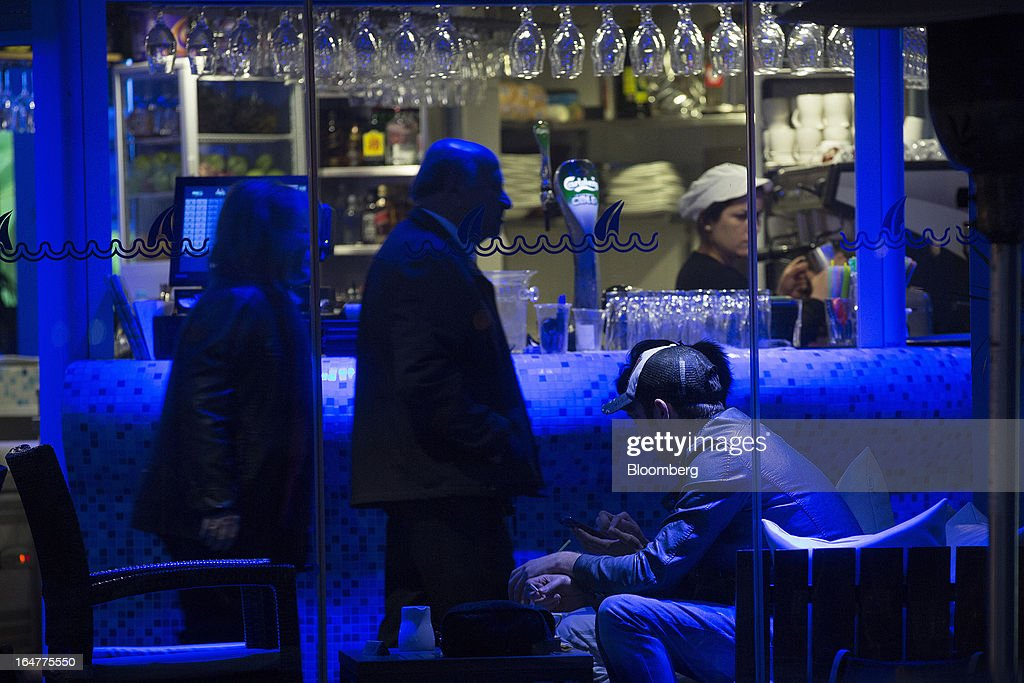 Customers are seen illuminated with blue light at a waterfront bar in Limassol, Cyprus, on Wednesday, March 27, 2013. The ECB said on March 25 it won't stop the Cypriot central bank from providing the island's banking sector with emergency funding. Photographer: Simon Dawson/Bloomberg via Getty Images