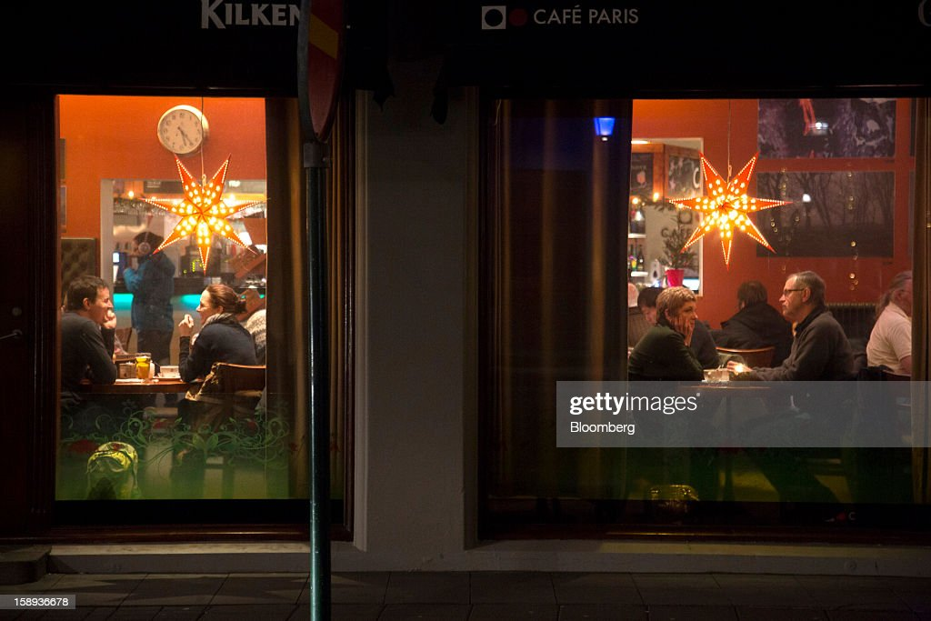 Customers are seen through a cafe window in Reykjavik, Iceland, on Tuesday, Jan. 1, 2013. Iceland's inflation rate eased in December as central bank efforts to stabilize the krona with interest rate increases paid off. Photographer: Arnaldur Halldorsson/Bloomberg via Getty Images