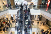 Customers are seen traveling on escalators as they shop for discounted goods in the Christmas sales at the Westfield Stratford City mall in this...