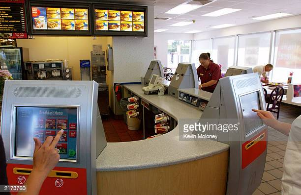 Customers at a McDonald's store place orders and pay through a new kiosk system being tested in five Denver area stores July 18 2003 in Littleton...