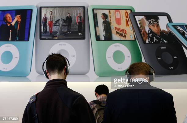 Customers at an Apple Store wear headphones as they listen to new Apple iPod nanos October 22 2007 in San Francisco California Apple stock surged...