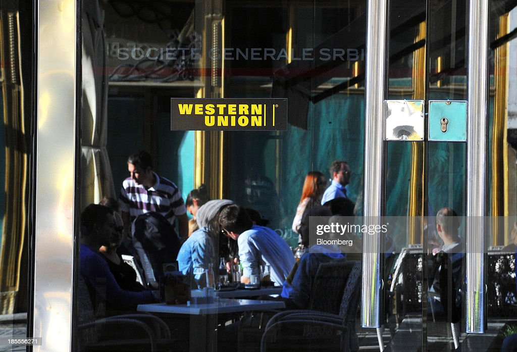 Customers at an outdoor cafe are seen reflected in the window of a Western Union Co. branch in Belgrade, Serbia, on Sunday, Oct. 20, 2013. Serbia's government revealed a salvo of measures to bring the public finance deficit and debt back under control by 2017 after the head of the largest coalition party warned the country was on the brink of insolvency. Photographer: Oliver Bunic/Bloomberg via Getty Images