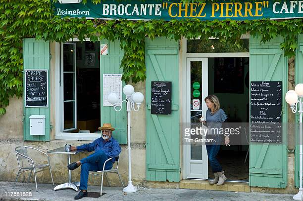 Customers at traditional French Cafe with menus in quaint town of Castelmoron d'Albret in Bordeaux region Gironde France