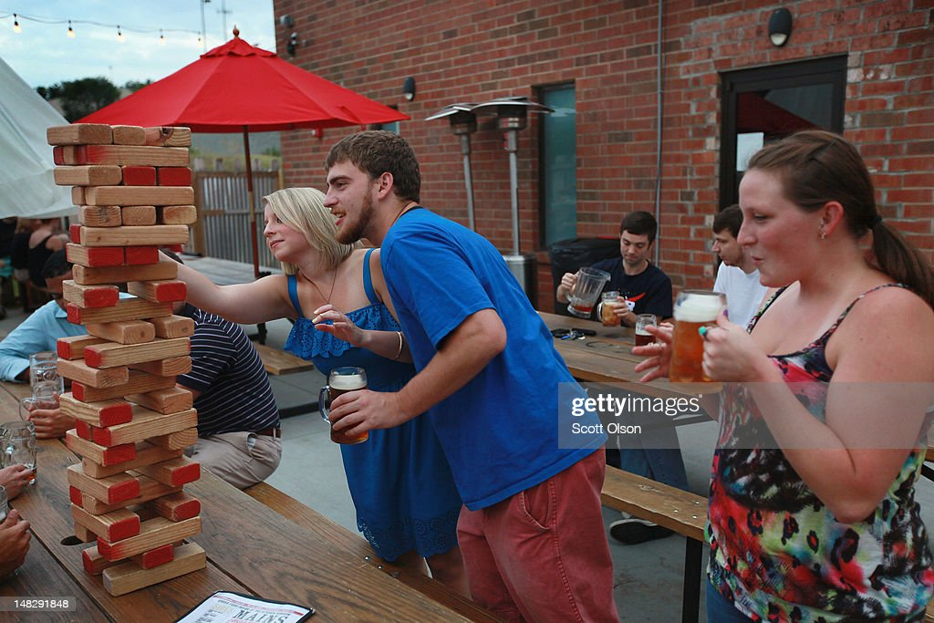 Customers at VBGB play an oversized Jenga-type game while having a beer in the beer garden on July 12, 2012 in Charlotte, North Carolina. In addition to the Jenga-type game, the beer hall and garden, located in the NC Music Factory, also has an oversized chess game, table tennis, bean bags and other games for customers to play while drinking or eating. The NC Music Factory, located on the grounds of a former textile factory, houses several bars restaurants and entertainment venues. Businesses in Charlotte are anticipating a boost in sales when an estimated 35,000 visitors arrive in the city for the 2012 Democratic National Convention (DNC) September 3-6.