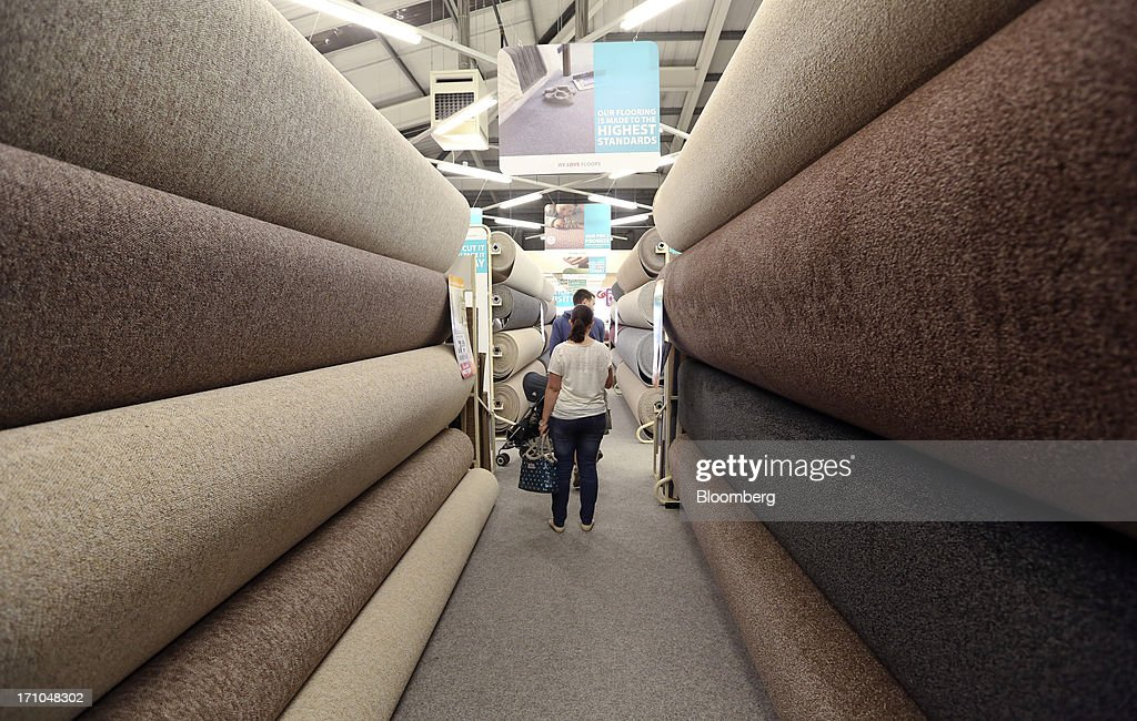 Customers browse a display of carpet rolls inside a Carpetright Plc store in Basildon, U.K., on Friday, June 21, 2013. U.K. retail sales rose more than economists forecast in May as consumers spent more online and food sales increased at their fastest pace for more than two years. Photographer: Chris Ratcliffe/Bloomberg via Getty Images