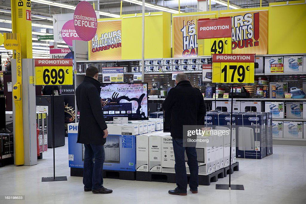 Customers browse a display of flat-screen televisions in the electronics department inside a Carrefour SA supermarket in Portet sur Garonne, near Toulouse, France, on Tuesday, March 5, 2013. Carrefour's stock has risen 47 percent since Georges Plassat's arrival as chief executive officer, partially offsetting a 71 percent decline in the preceding five years. Photographer: Balint Porneczi/Bloomberg via Getty Images