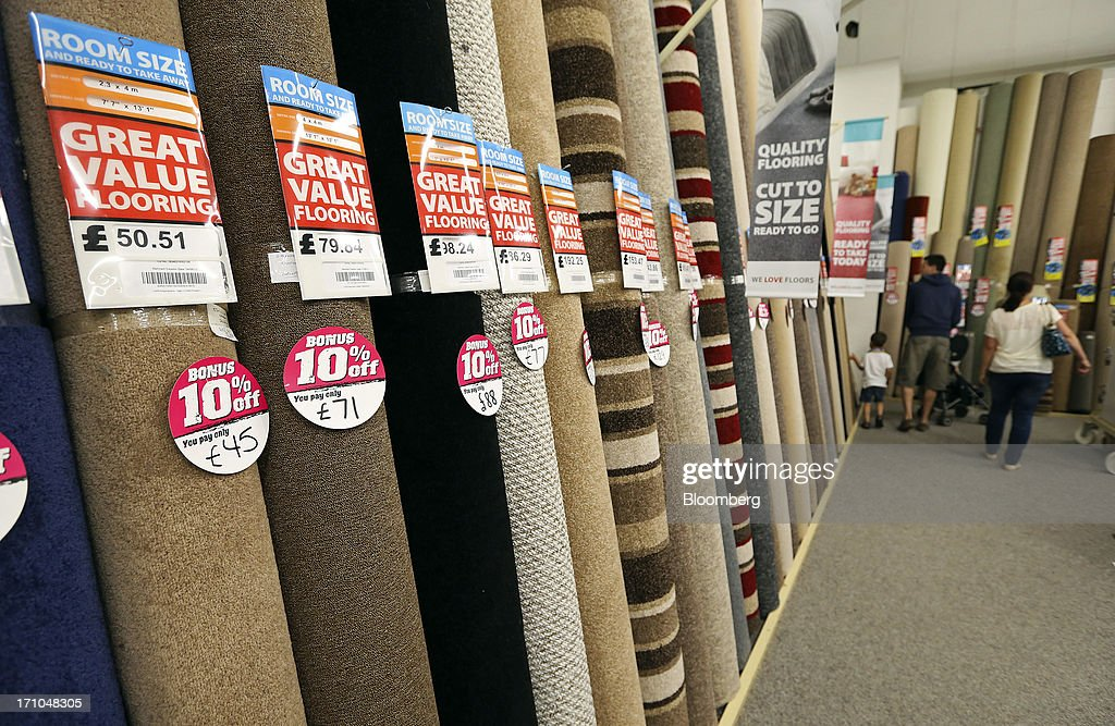 Customers browse a display of pre-cut carpet rolls inside a Carpetright Plc store in Basildon, U.K., on Friday, June 21, 2013. U.K. retail sales rose more than economists forecast in May as consumers spent more online and food sales increased at their fastest pace for more than two years. Photographer: Chris Ratcliffe/Bloomberg via Getty Images