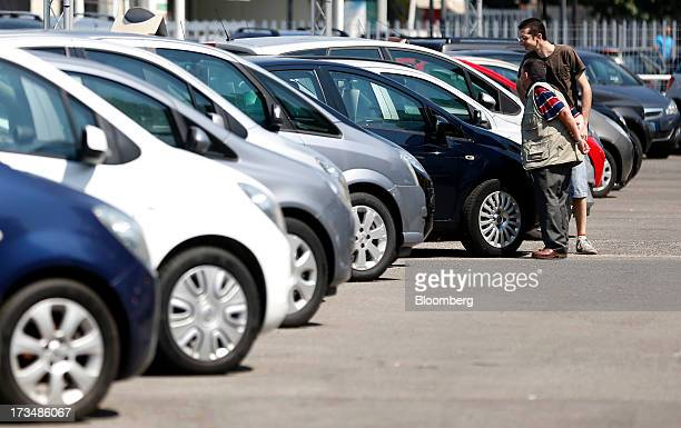 Customers browse a display of second hand automobiles displayed for sale outside a car dealership in Rome Italy on Saturday July 13 2013 European car...