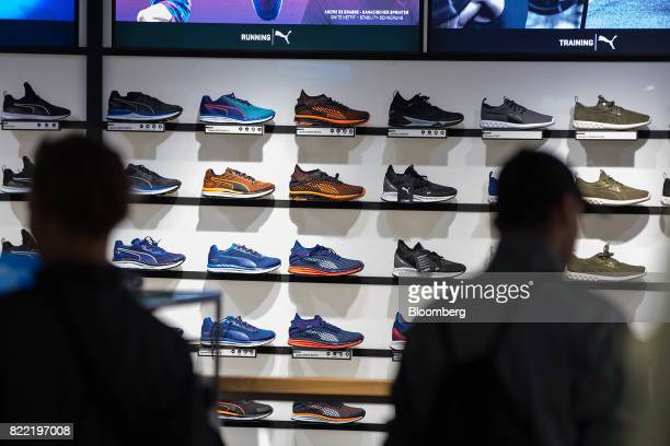 Customers browse a men's running shoe display inside a Puma SE sportswear clothing store in Berlin Germany on Tuesday July 25 2017 Puma increased its...