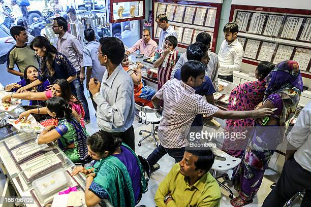 Customers browse and talk to salespeople inside the Umedmal Tilokchand Zaveri jewelry store during the festival of Dhanteras two days before Diwali...