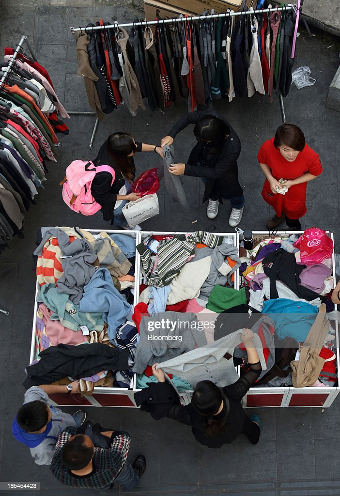 Customers browse clothing at a street stall in Wuhan, China, on Sunday, Oct. 20, 2013. China's economic expansion accelerated to 7.8 percent in the third quarter from a year earlier, the statistics bureau said Oct. 18, reversing a slowdown that put the government at risk of missing its 7.5 percent growth target for 2013. Photographer: Tomohiro Ohsumi/Bloomberg via Getty Images