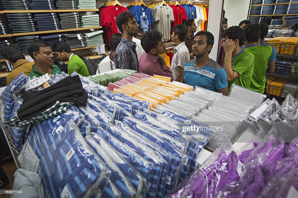 Customers browse clothing at the opening of a Grameen Uniqlo store, a joint venture between Fast Retailing Co. and Grameen Healthcare Trust, in the Paltan area of Dhaka, Bangladesh, on Saturday, Oct. 5, 2013. Fast Retailing, Asia's biggest clothing retailer, set up the venture with Grameen Healthcare Trust to design, make and sell clothes in Bangladesh. Photographer: Jeff Holt/Bloomberg via Getty Images
