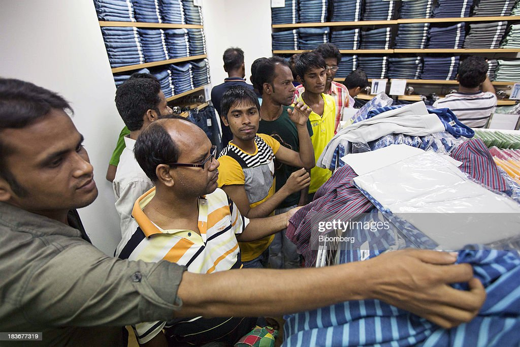 Customers browse clothing during the opening of a Grameen Uniqlo store, a joint venture between Fast Retailing Co. and Grameen Healthcare Trust, in the Paltan area of Dhaka, Bangladesh, on Saturday, Oct. 5, 2013. Fast Retailing, Asia's biggest clothing retailer, set up the venture with Grameen Healthcare Trust to design, make and sell clothes in Bangladesh. Photographer: Jeff Holt/Bloomberg via Getty Images
