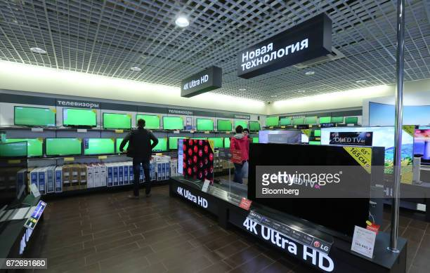 Customers browse digital television screens including a display of 4K ultra HD Oled products by LG Electronics Inc inside an MVideo PJSC electronics...