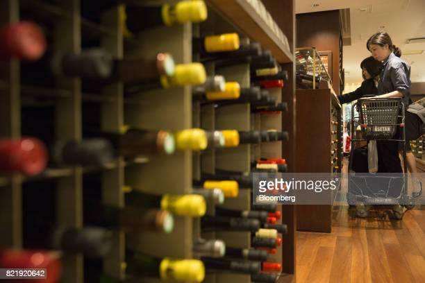 Customers browse European wines on display at the Isetan Shinjuku department store operated by Isetan Mitsukoshi Holdings Ltd in Tokyo Japan on...