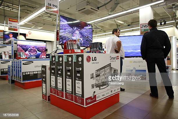 Customers browse flatscreen and high definition televisions including products by LG Electronics Inc and Samsung Electronics Co for sale inside an M...