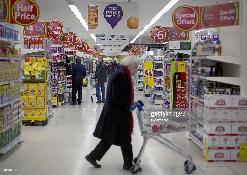 Customers browse for goods inside a Tesco Plc supermarket in the borough of Kensington in London, U.K., on Tuesday, March 12, 2013. Tesco Plc, the U.K.'s largest grocer launched a 'Price Promise', its latest initiative offering to match the price of customers' purchases to that of it's rivals, including Wal-Mart Stores Inc.'s ASDA. Photographer: Simon Dawson/Bloomberg via Getty Images