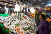Customers browse fresh fish for sale at a market stall in Istanbul Turkey on Sunday Jan 5 2014 The Turkish lira is poised to rebound after a...