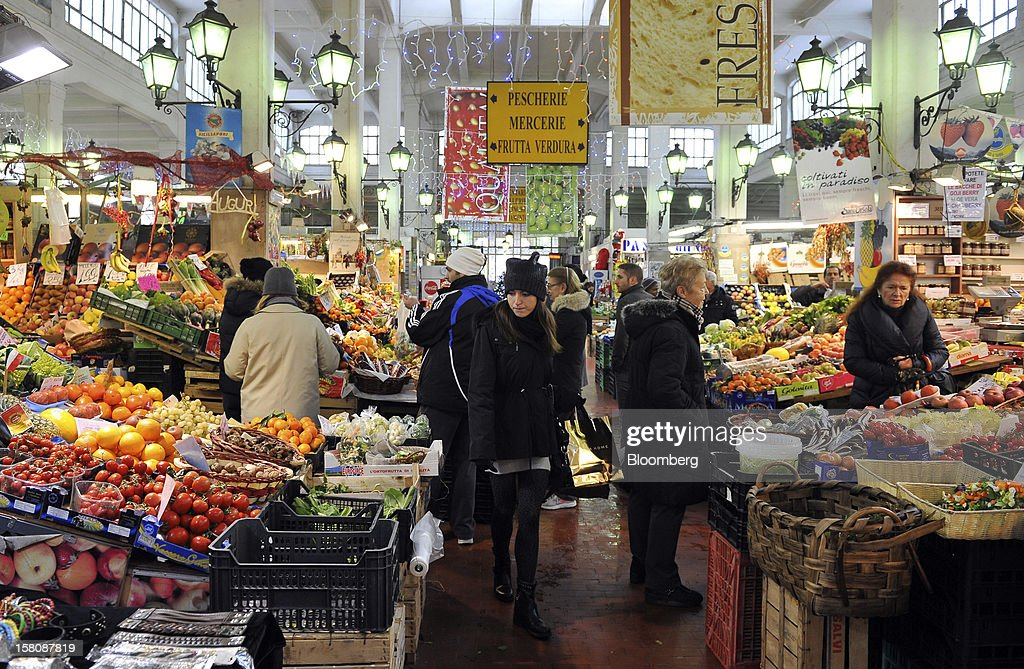 Customers browse fruit and vegetable goods displayed on stalls at the Prati indoor market in Rome, Italy, on Monday, Dec. 10, 2012. The imminent end of Prime Minister Mario Monti's government fueled the largest increase in Italian borrowing costs in four months and threatened to open a new front in Europe's crisis fight before a year-end summit. Photographer: Victor Sokolowicz/Bloomberg via Getty Images