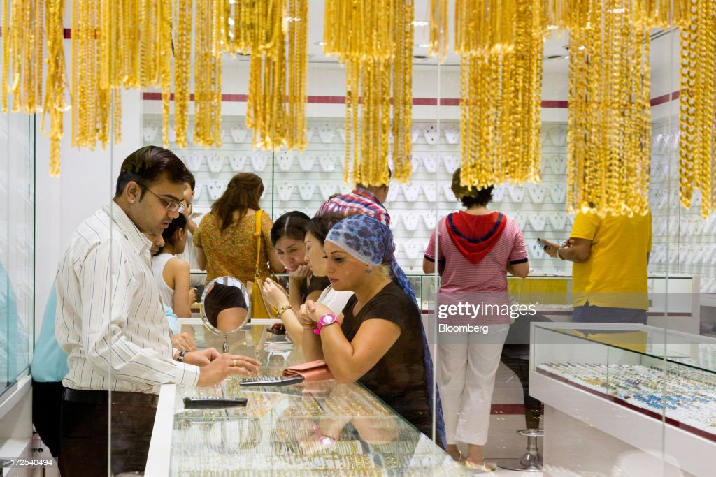 Customers browse gold jewelry and negotiate prices inside a gold store in the Dubai Gold Souk in the Deira district of Dubai, United Arab Emirates, on Tuesday, July 2, 2013. Gold swung between gains and losses in London as investors weighed prospects for increased physical demand against a slowing stimulus in the U.S. Photographer: Duncan Chard/Bloomberg via Getty Images