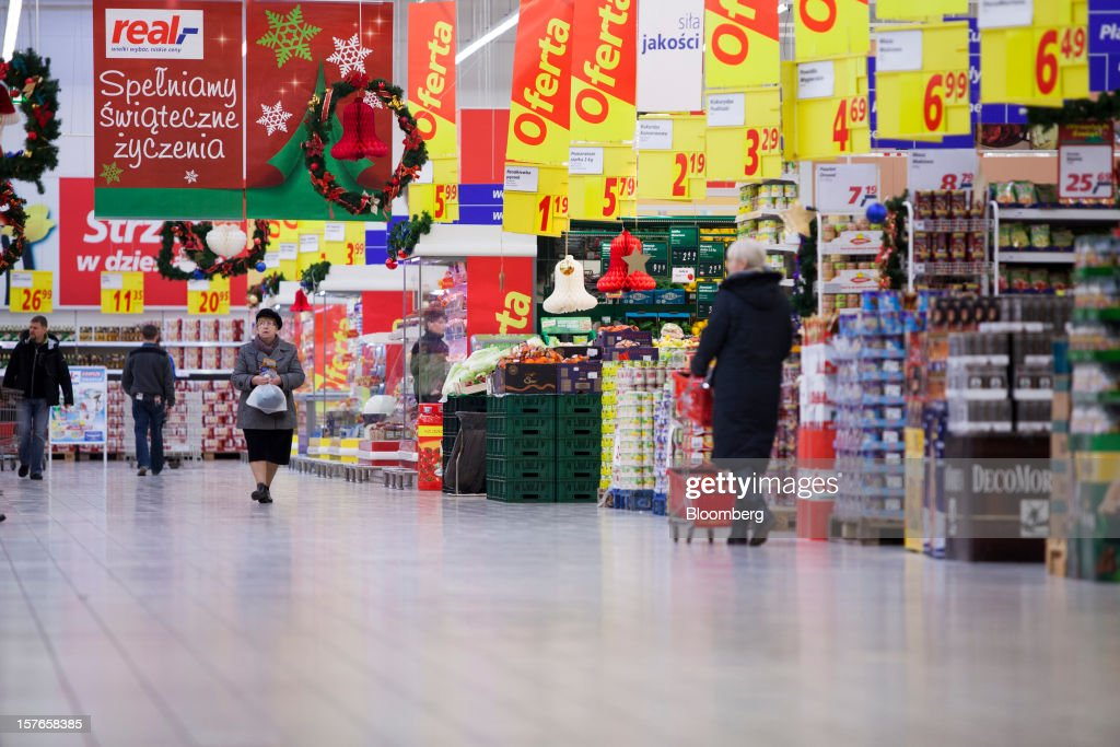 Customers browse goods beneath discounted product signs inside a Real supermarket in Wroclaw, Poland, on Wednesday, Dec. 5, 2012. Metro AG, Germany's biggest retailer, agreed to sell its Real grocery stores in eastern Europe to Groupe Auchan SA of France for 1.1 billion euros ($1.4 billion) in Chief Executive Officer Olaf Koch's first big deal since taking the helm. Photographer: Bartek Sadowski/Bloomberg via Getty Images