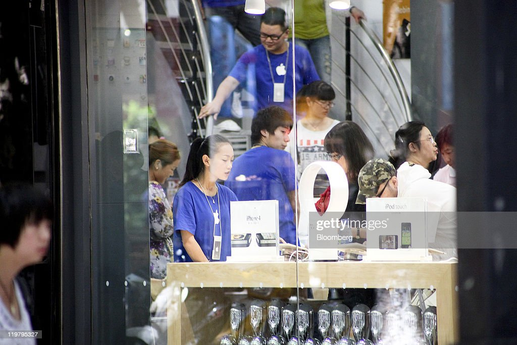Customers browse inside a store which sells Apple Inc. products, without the company's authorization, in Kunming, Yunnan Province, China, on Monday, July 25, 2011. Apple operates four stores in China, all in Beijing and Shanghai, and has more than 900 authorized sales agents across the country in addition to a distribution agreement with carrier partner China Unicom (Hong Kong) Ltd. Photographer: Nelson Ching/Bloomberg via Getty Images