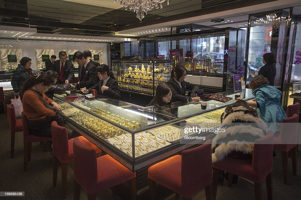 Customers browse jewelry in a Chow Tai Fook Jewellery Group Ltd. store in the Central district of Hong Kong, China, on Wednesday, Jan. 16, 2013. Chow Tai Fook Jewellery, the world's biggest jeweler by market value, posted an 8 percent drop in third-quarter same-store sales as Chinese shoppers curbed spending amid a slower economy. Photographer: Jerome Favre/Bloomberg via Getty Images