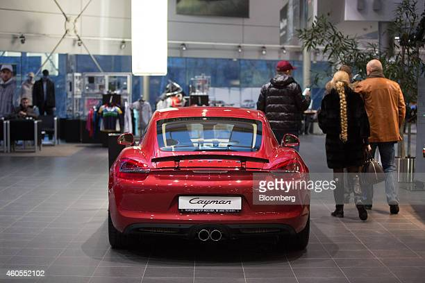 Customers browse luxury sportscars including a Porsche Cayman model for sale inside a Porsche AG new automobile dealership in Moscow Russia on Monday...