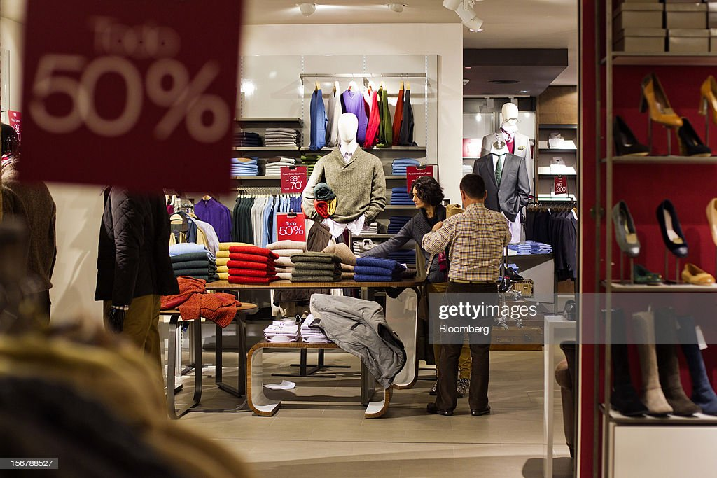 Customers browse men's clothing on display near discounted price signs inside a Cortefiel SA store in Majadahonda, near Madrid, Spain, on Tuesday, Nov. 20, 2012. Bank of Spain Governor Luis Maria Linde said the government risks missing its budget targets this year and next, adding to doubts on Prime Minister Mariano Rajoy's ability to cut the deficit amid a five-year slump. Photographer: Angel Navarrete/Bloomberg via Getty Images
