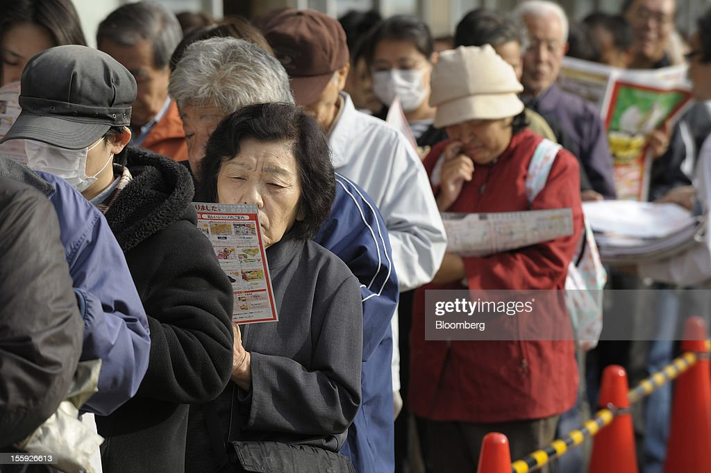 Customers browse pamphlets as they wait in line for the opening of an Aeon Co. shopping center in Tokyo, Japan, on Friday, Nov. 9, 2012. Aeon Co. is Japan's largest supermarket operator. Photographer: Akio Kon/Bloomberg via Getty Images