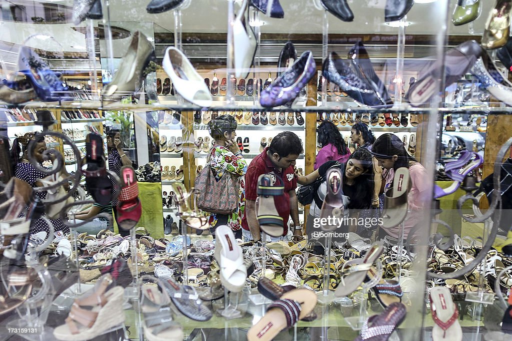 Customers browse shoes displayed for sale at a Citywalk footwear store in the suburb of Bandra in Mumbai, India, on Saturday, July 6, 2013. India's consumer price index (CPI) figures for June are scheduled to be released on July 12. Photographer: Dhiraj Singh/Bloomberg via Getty Images