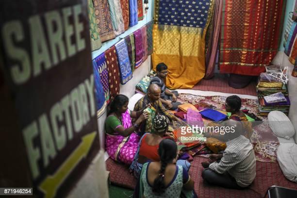 Customers browse silk sarees at a store in Varanasi Uttar Pradesh India on Saturday Oct 28 2017 In Varanasi where the manufacture of 45meter sarees...