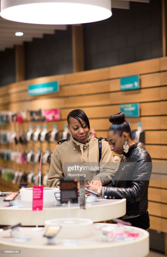 Customers browse smartphone handsets inside an EE (Everything Everywhere) store, a joint venture between France Telecom SA and Deutsche Telekom AG, in Stratford, U.K., on Monday, Dec. 5, 2012. France Telecom CEO Stephane Richard said in an interview last month that the Paris-based company has received interest from private-equity firms seeking a minority stake in the 50-50 venture, and may also consider an initial public offering of the unit. Photographer: Jason Alden/Bloomberg via Getty Images
