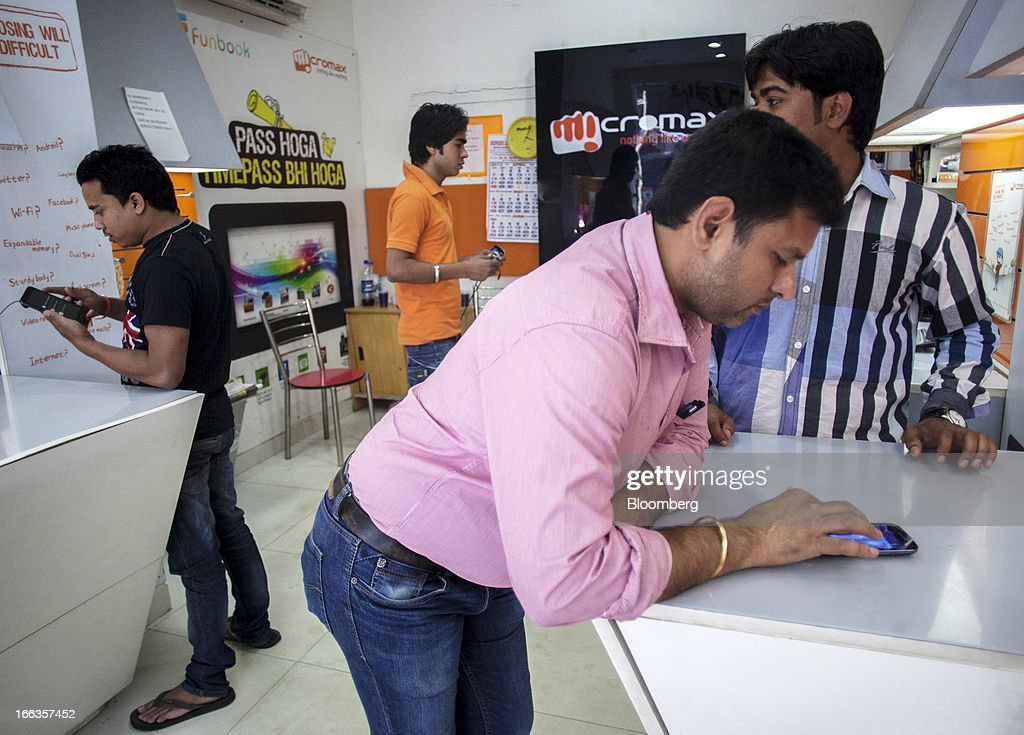 Customers browse smartphones at a MicroMax Informatics Ltd. store in New Delhi, India, on Tuesday, April 9, 2013. Apple Inc. and Samsung Electronics Co. are being outpaced in the fast-growing Indian smartphone market by aggressive local competitors Micromax and Karbonn Mobiles India Pvt. Ltd. Photographer: Prashanth Vishwanathan/Bloomberg via Getty Images