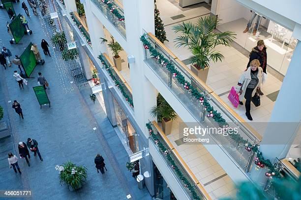 Customers browse stores inside the Galerija Centrs shopping mall in Riga Latvia on Tuesday Dec 10 2013 The country of 2 million will become the 18th...