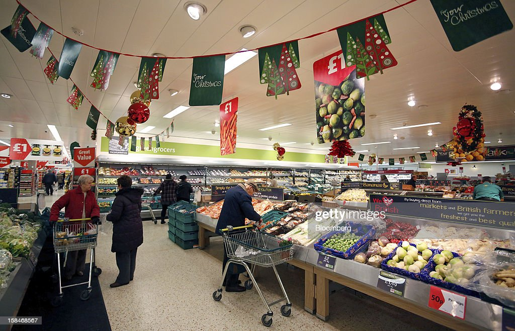 Customers browse the fresh fruit and vegetable section inside a Morrisons supermarket, operated by William Morrisons Supermarkets Plc, in Chadderton, U.K., on Monday, Dec. 17, 2012. The British Christmas is the biggest epicurean occasion of the year, with households spending a total of 4 billion pounds on food in the final week before Dec. 25. Photographer: Paul Thomas/Bloomberg via Getty Images