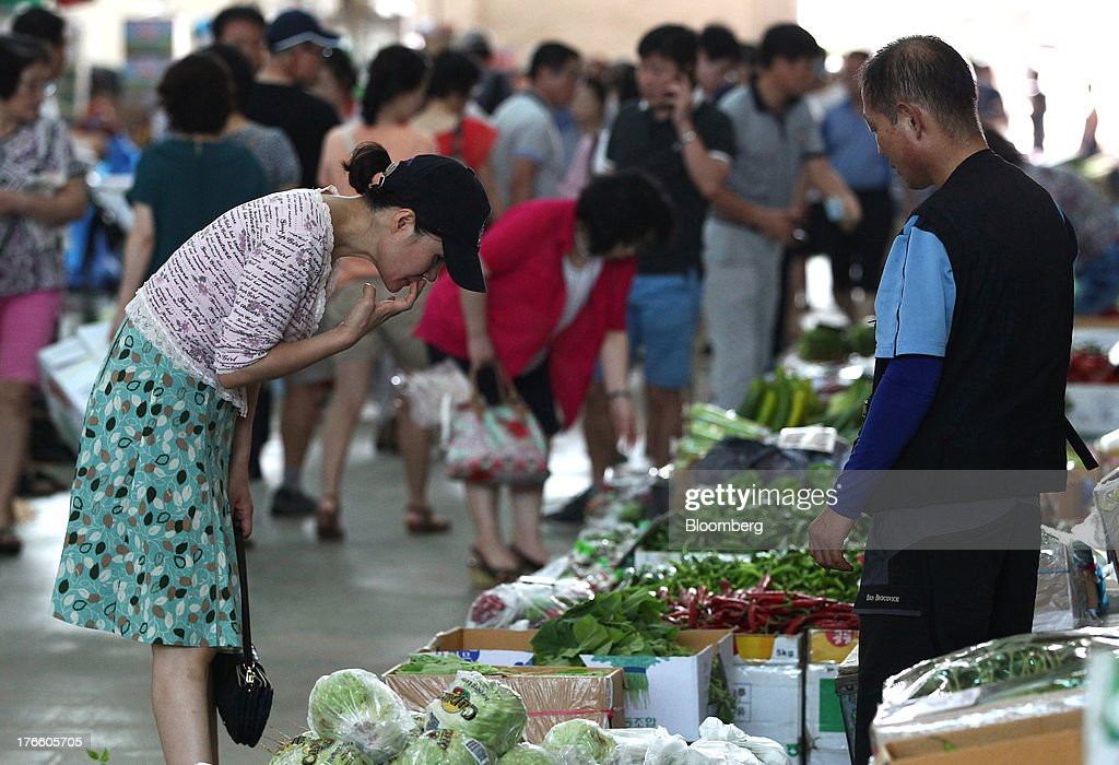 Customers browse vegetables at Samsan Agricultural Wholesale Market in Incheon, South Korea, on Friday, Aug. 16, 2013. South Korean producer prices declined 0.9 percent in July from a year earlier after a 1.4 percent drop in June, the central bank said in a statement today. Photographer: SeongJoon Cho/Bloomberg via Getty Images